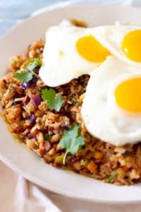 Closeup of bowl of fried rice topped with three sunny side up eggs.