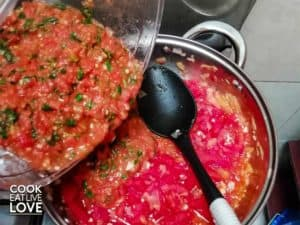 Chopped tomatoes and basil are being added back to pan.