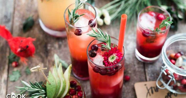 Collection of holiday beverages garnished with cranberries, pine and flowers.