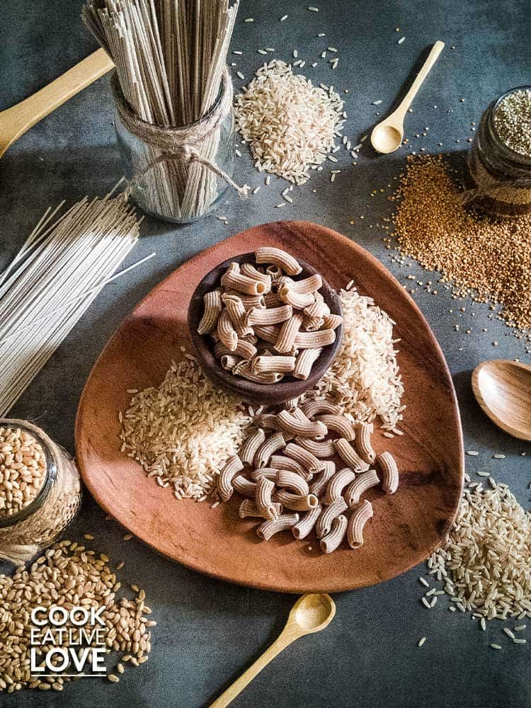 Overhead shot of various whole grains to use in mix and match meal prep includes quinoa pasta, brown rice, soba noodles and quinoa.