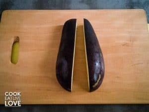 Eggplant on wood cutting board cut in half.