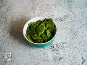 Small bowl shows snow peas cut into ½ inch pieces cut on an angle.