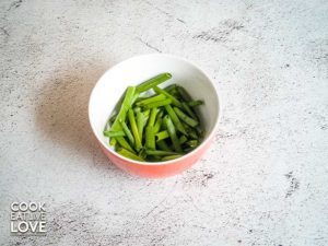 Bowl shows ½ inch pieces of green onion cut on an angle.