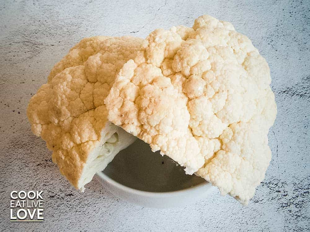 Photo of cauliflower head in a bowl on concrete background.