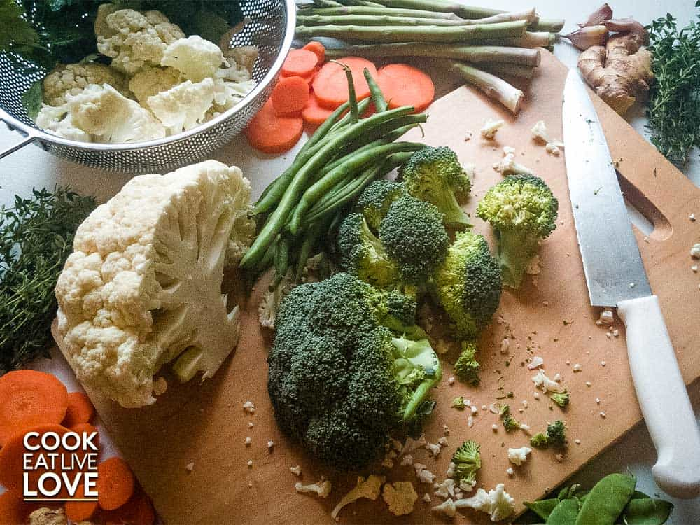 In this photo vegetables are on cutting board, being cut to make steamed veggies