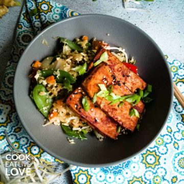 A bowl of food on a plate, with Cauliflower and Tofu