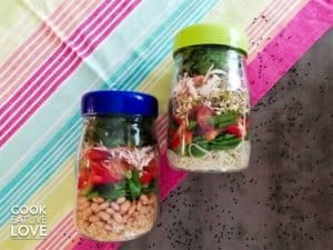 Asian lunch bowls are shown packed up to go in jars.
