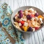 Greek pasta bowl with tofu feta on white wood background! All ready to eat.