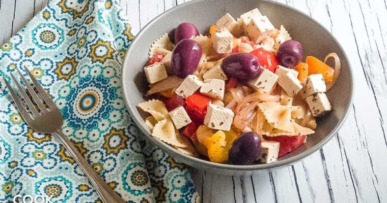 Greek pasta bowl with tofu feta on white wood background! All ready to eat.