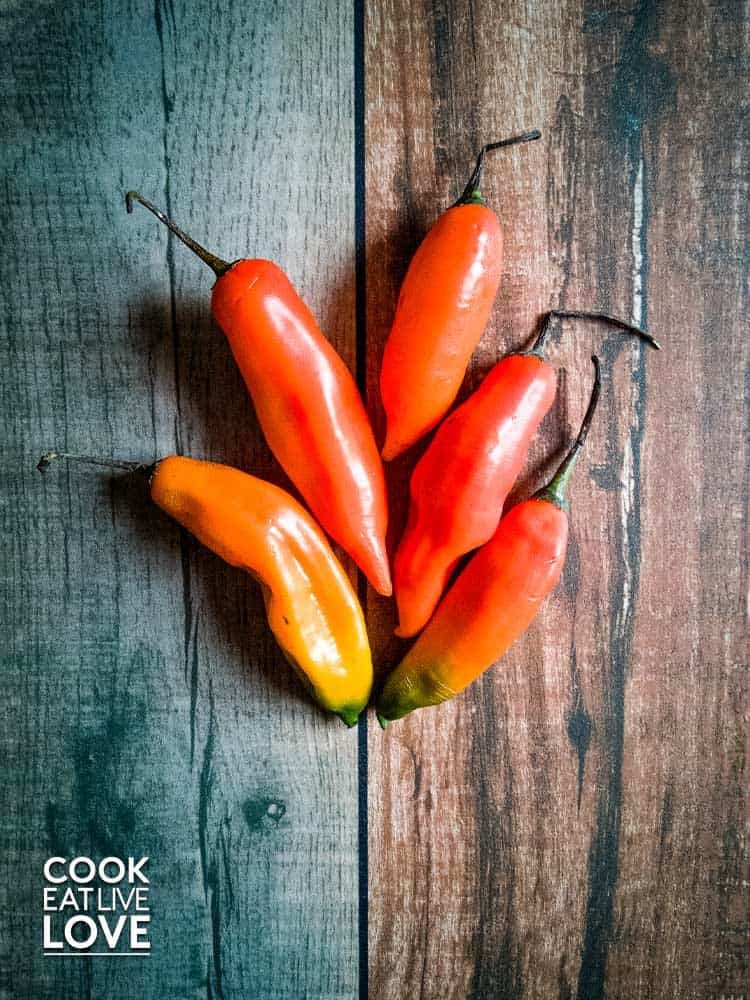 Photo of aji amarillo peppers on wood background demonstrating the variety of orange hues of this pepper.