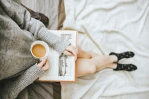 Woman reading book showing the importance of using quiet time as a self care technique to recharge.