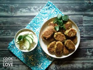 Mediterranean zucchini fritters are pictured with yogurt zip on white plate atop a gray and white background.
