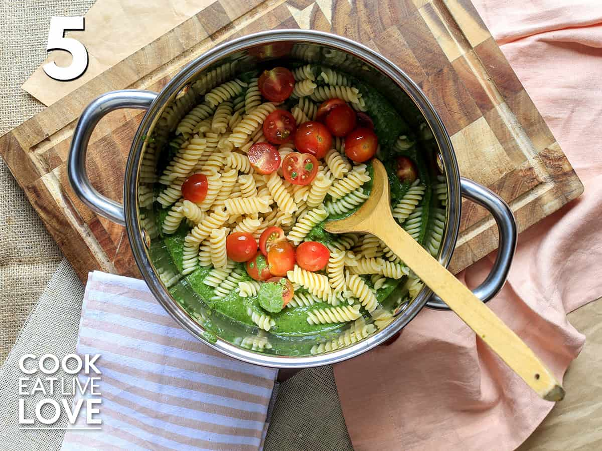 Pasta and tomatoes added to sauce in a pot