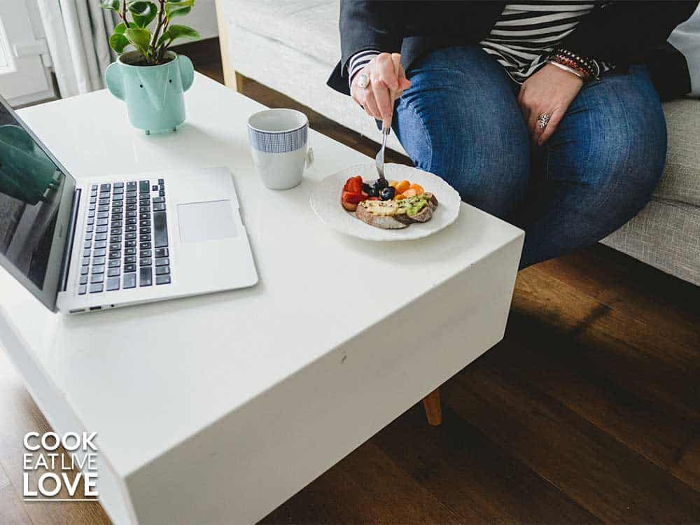 Person with only legs and hand showing sitting on couch eating a plate of food.
