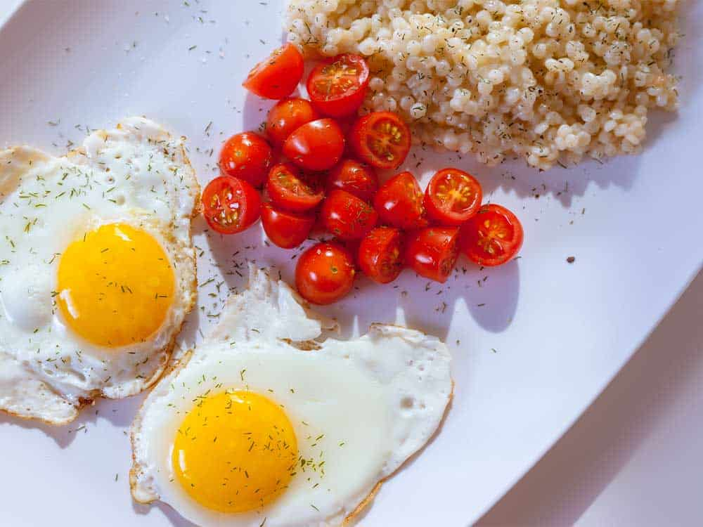 Healthy breakfast tips include a balance of macronutrients such as this plate with eggs, tomato and quinoa.
