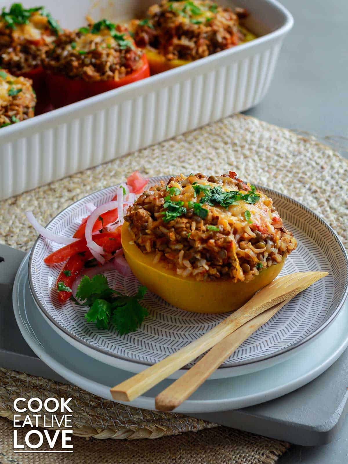 Lentil and brown rice peppers are topped with cheese and then baked in the oven.