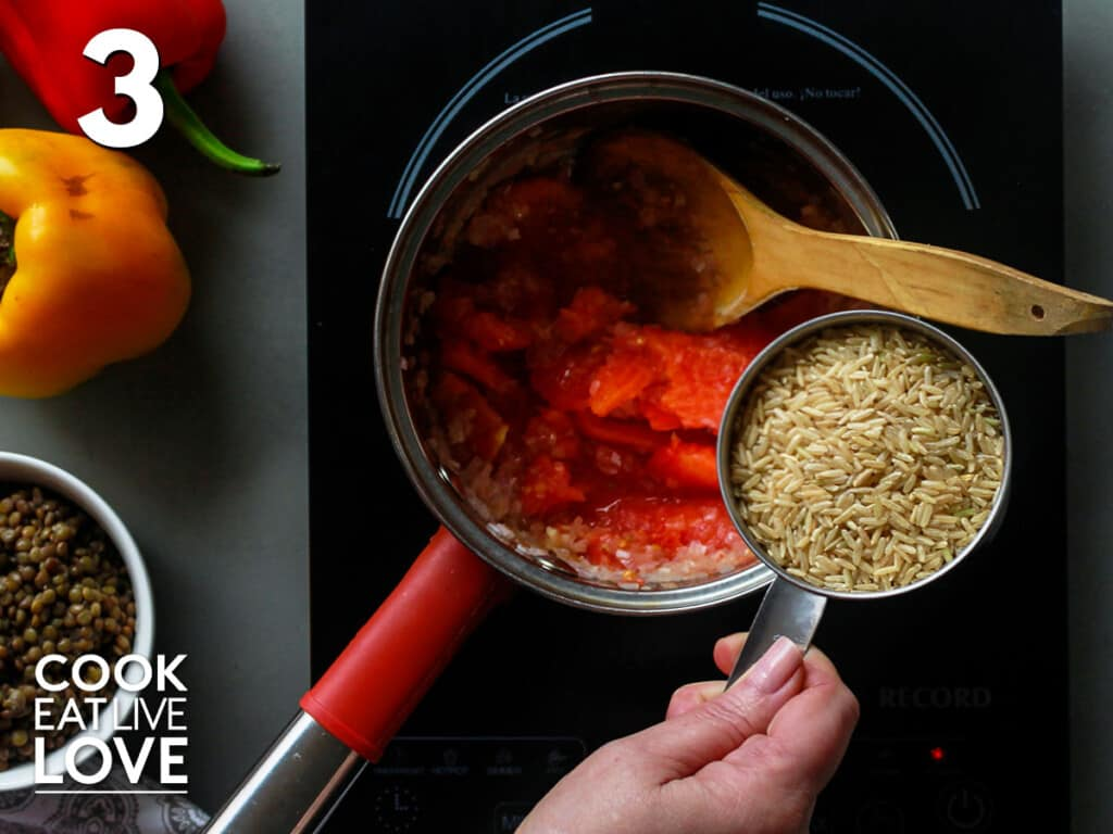 Adding rice to the pot with tomatoes and onions