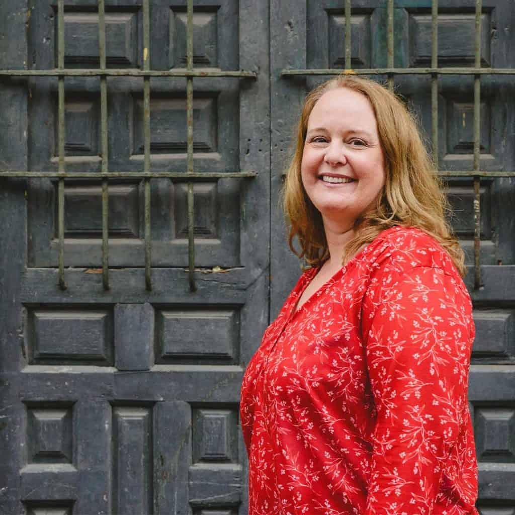 Lyn, blog author standing in front doors.
