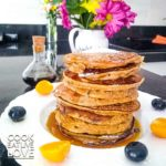 A plate topped with a vase of flowers on a table and plate of stacked pancakes