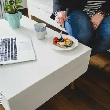 Hand reaching in with fork to pick up food on plate to eat computer on coffee table next to plate.