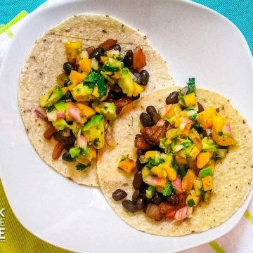 Black bean and mango tacos ready to eat on white plate.