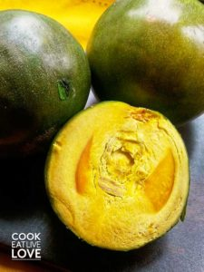Fresh lucuma whole and cut in half showing the bright yellow flesh.