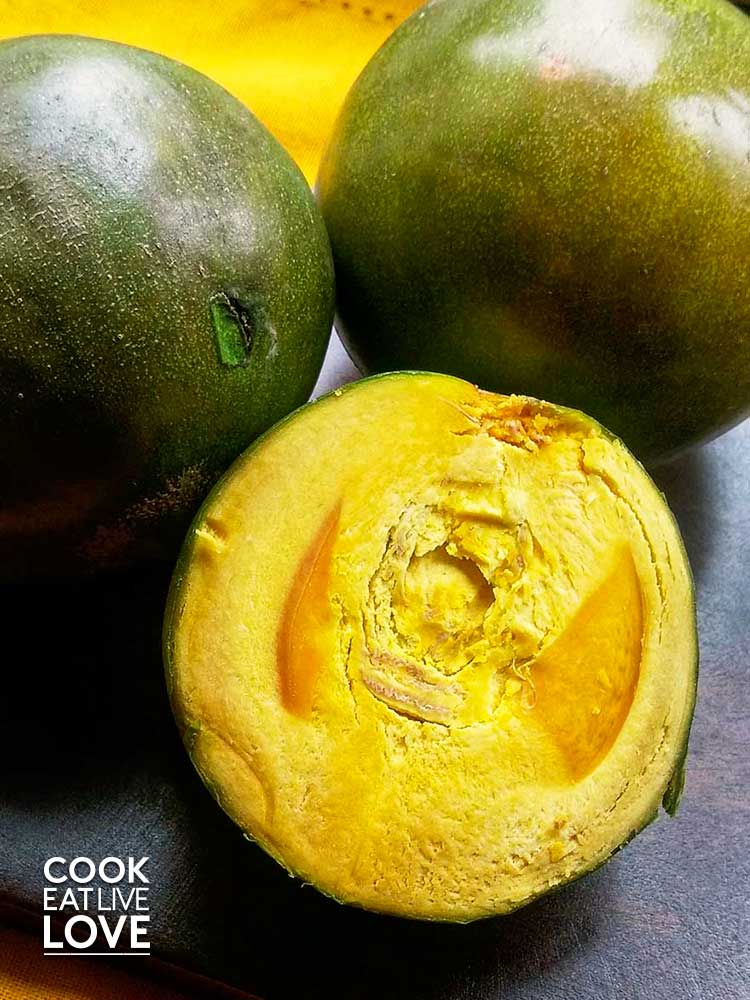 Lucuma fruit cut in half showing the brilliant yellow color.