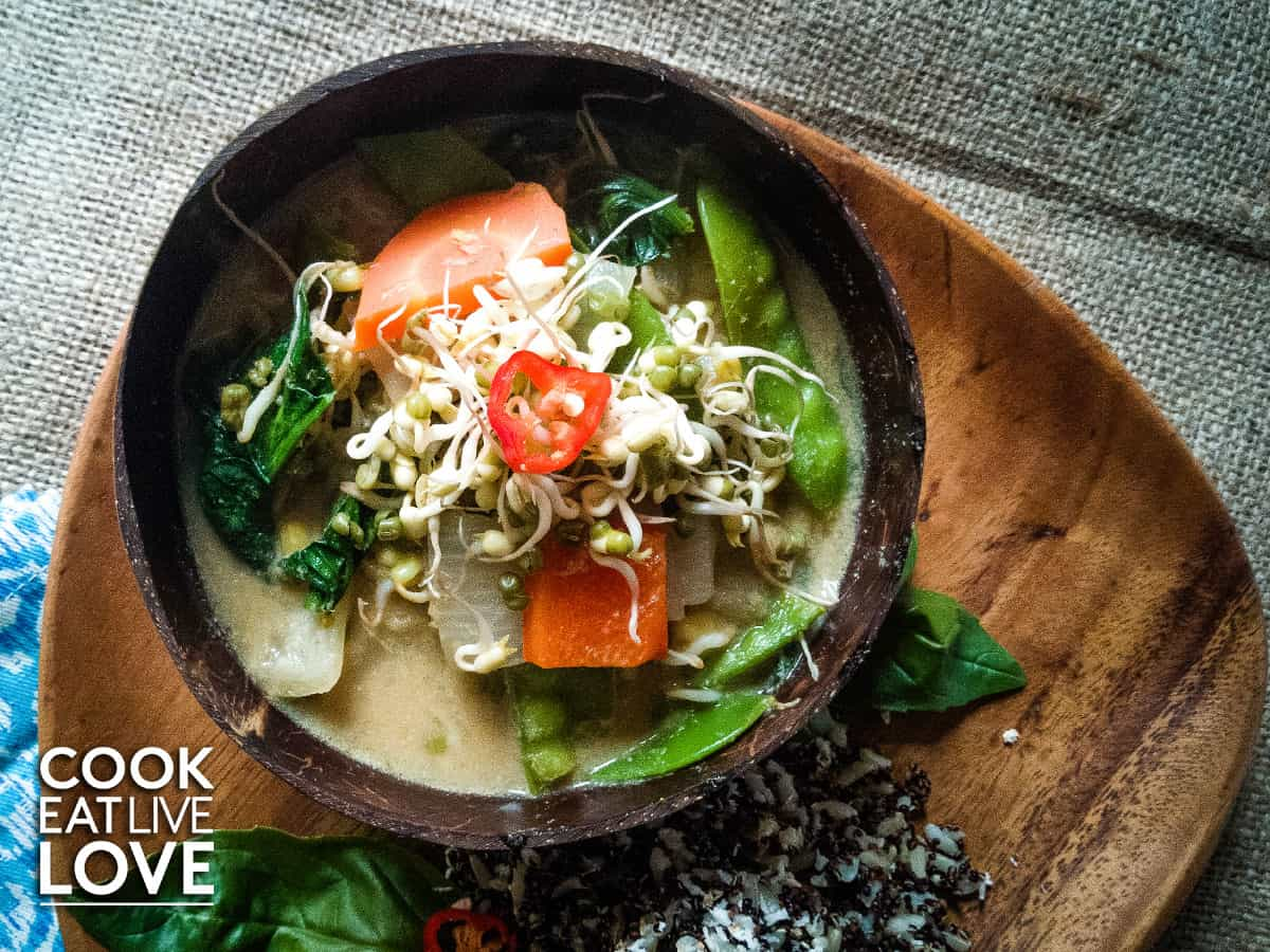 Vegan thai green curry is shown on table with spoon