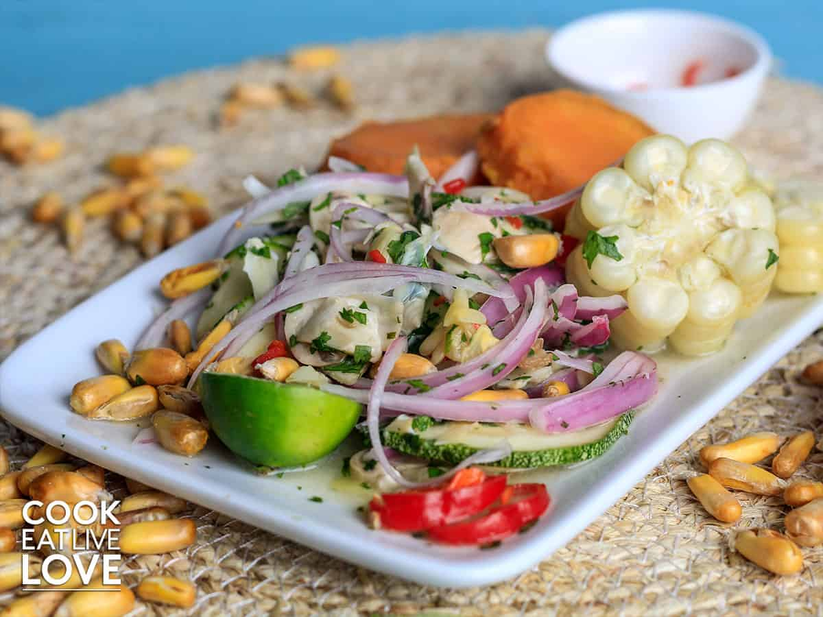 Vegan mixto ceviche is  shown on wooden plate accompanied by sweet potatoes and choclo.