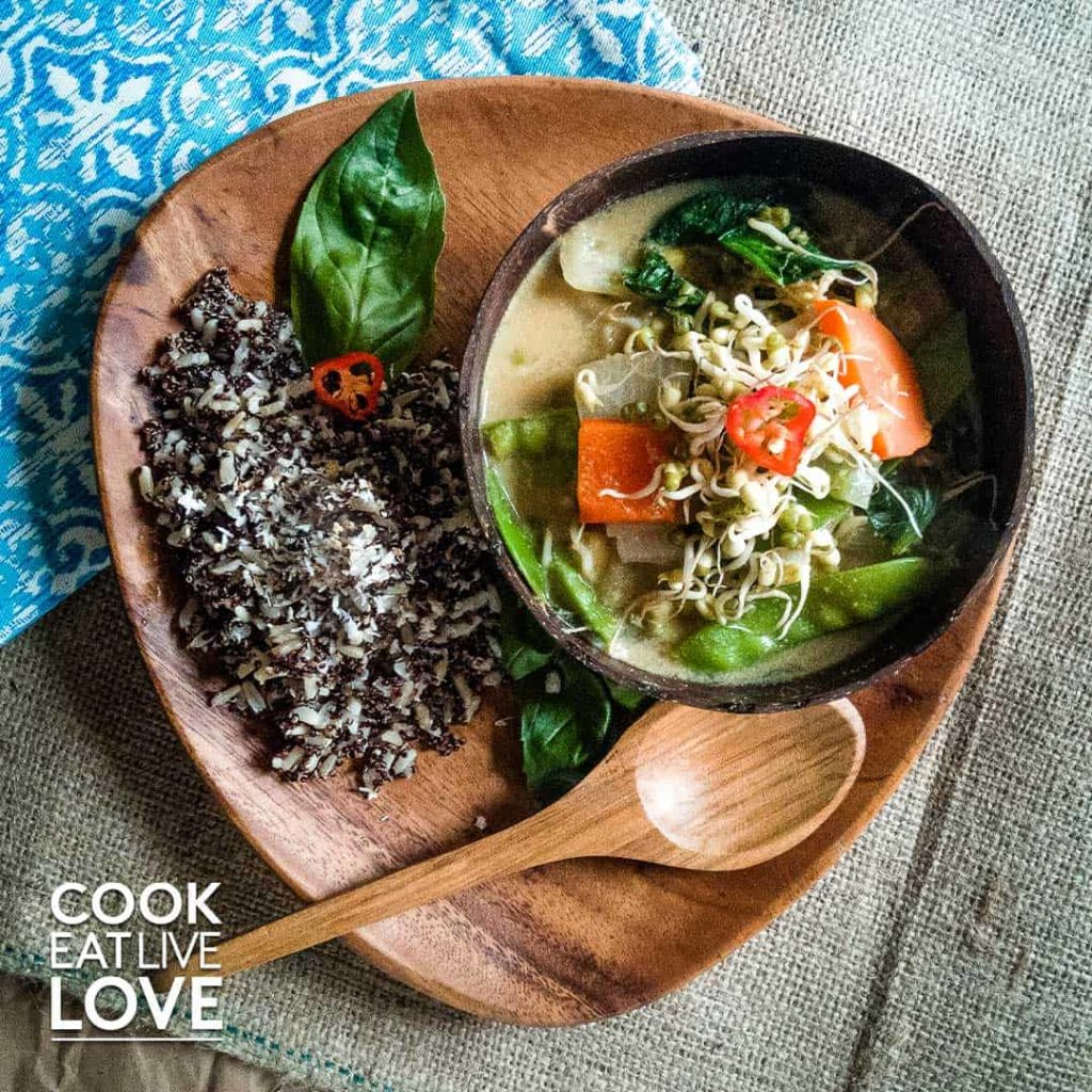 Vegan thai green curry is served up in a bowl with quinoa rice pilaf on the side.