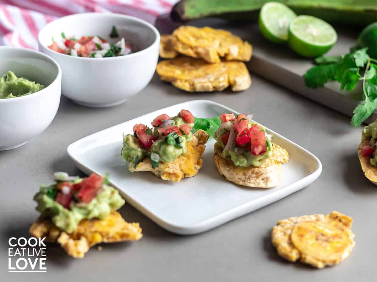 Baked tostones topped with mashed avocado and tomato salsa.