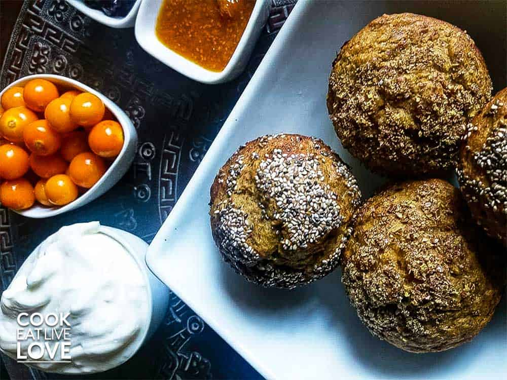 Fresh baked banana pumpkin muffins pictured with fruit, jam and yogurt.