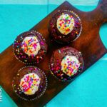 Finished whole wheat chocolate cupcakes on cutting board topped with multi-colored sprinkles.