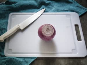 Peeled onion is shown on cutting board.