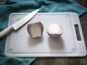 Onion cut in half lengthwise is shown on cutting board.