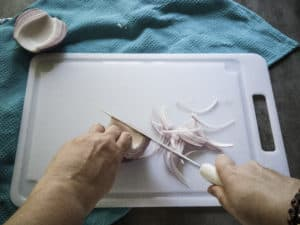 Demonstration of slicing onion feathers by slicing onion lengthwise.