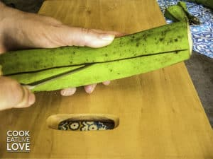 Peeling the green plantain with a knife.