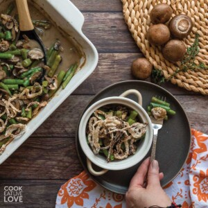Vegan green bean casserole in large casserole dish and small round casserole dish.