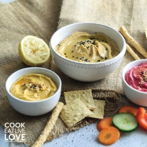 All three easy vegetable hummus served up in white bowls on the table