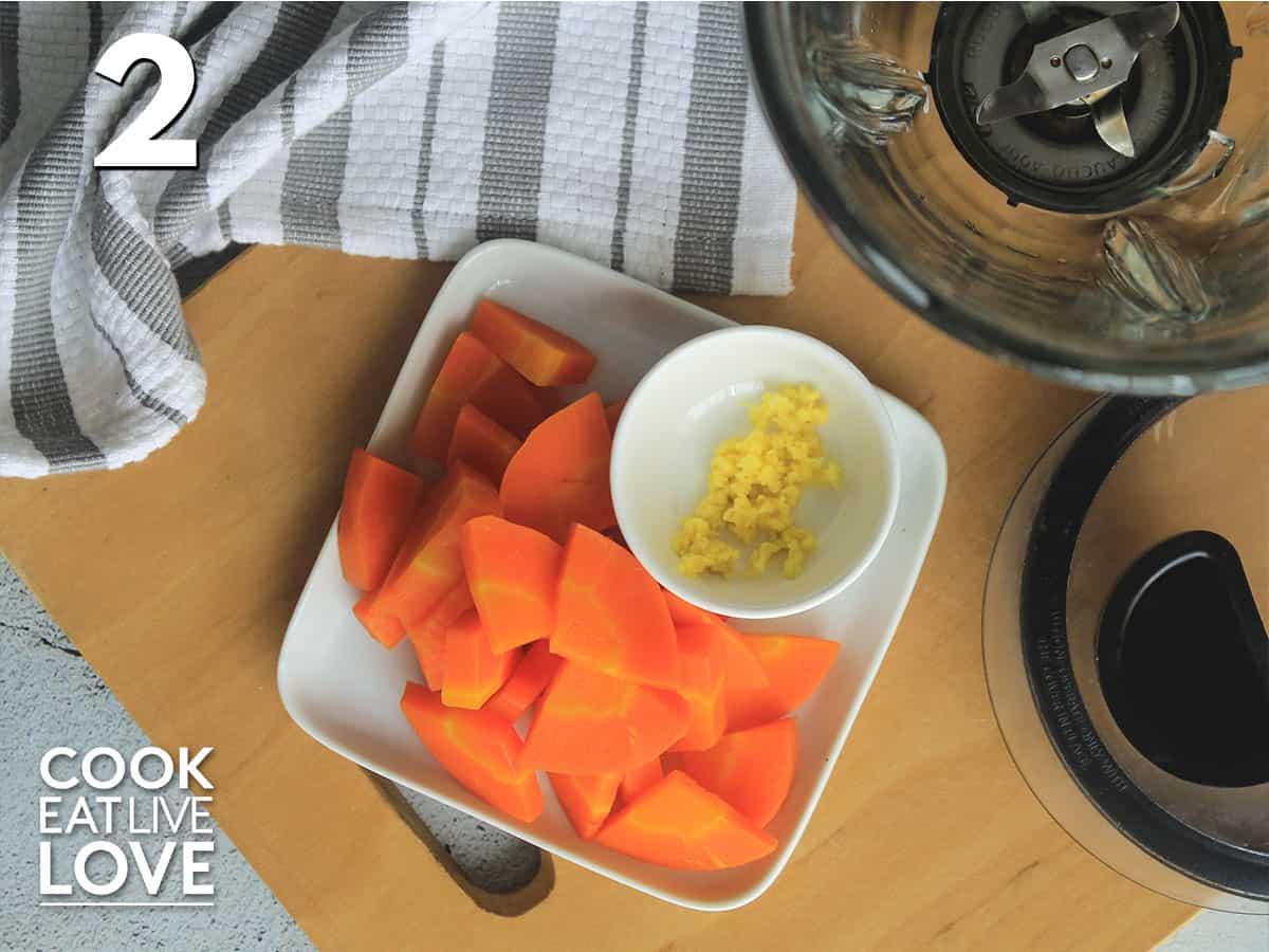Carrot and fresh ginger on fresh plate next blender