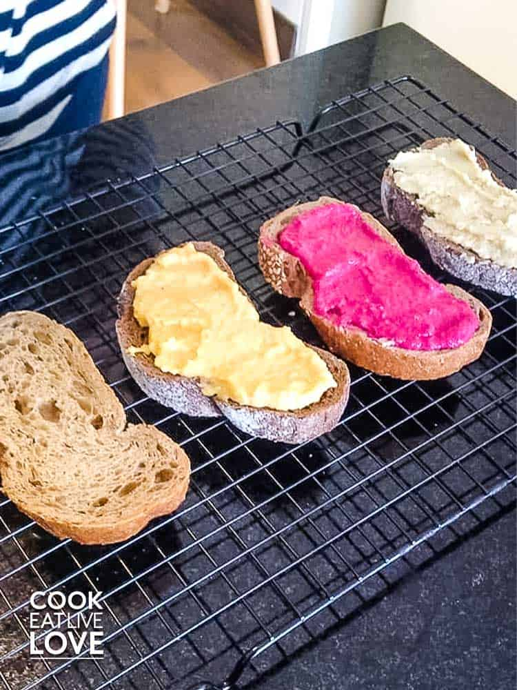 Building the toasts with easy vegetable hummus starts with spreading the bread.