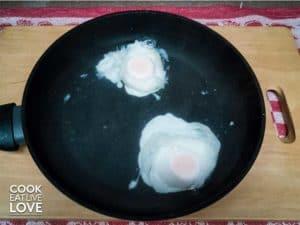 Eggs poaching in pan of water