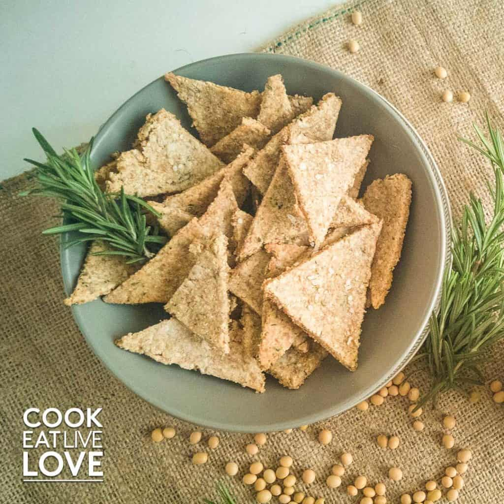 A bowl of crackers on burlap with soy beans and herbs