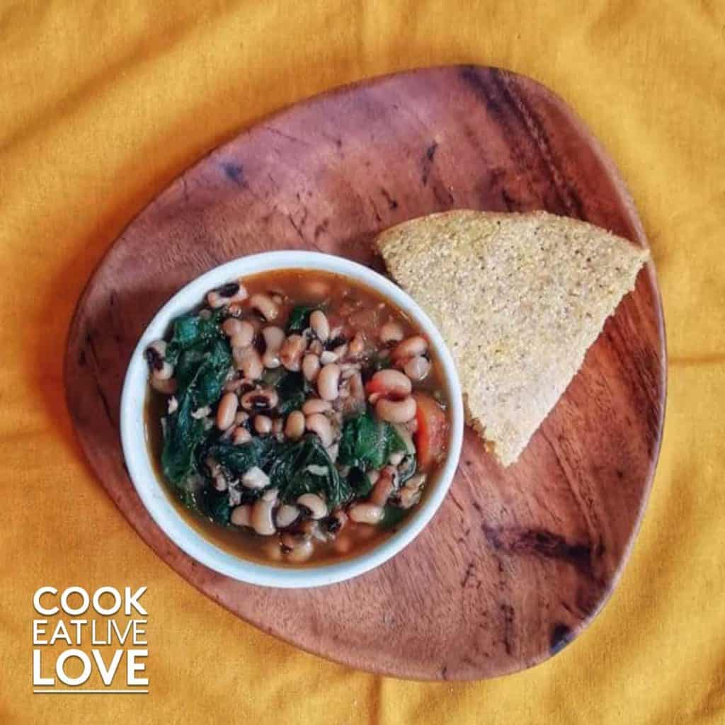 Black-eyed peas in a bowl with slice of cornbread next to it