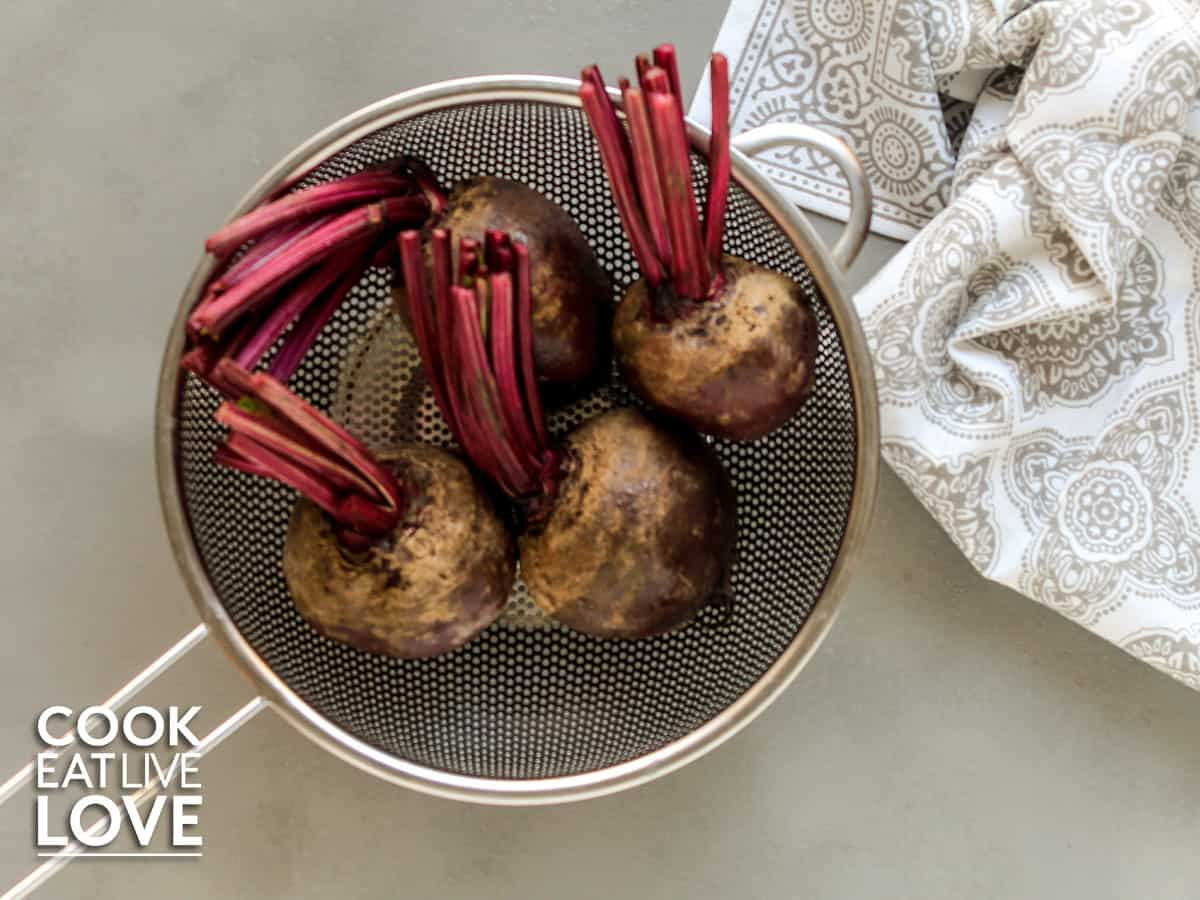 Fresh beets in a strainer on the counter