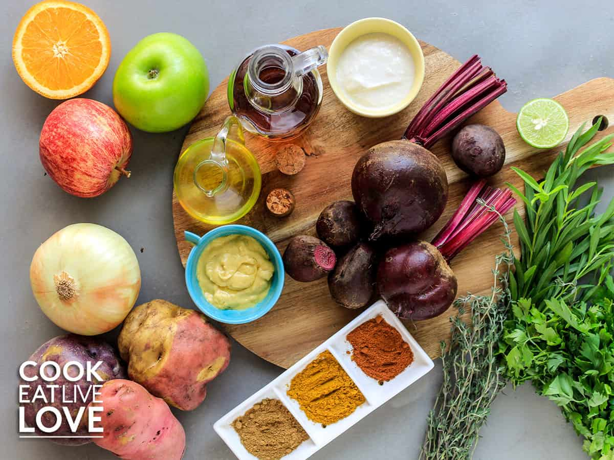 Beets on a cutting board surrounded by the best ingredients to cook with them