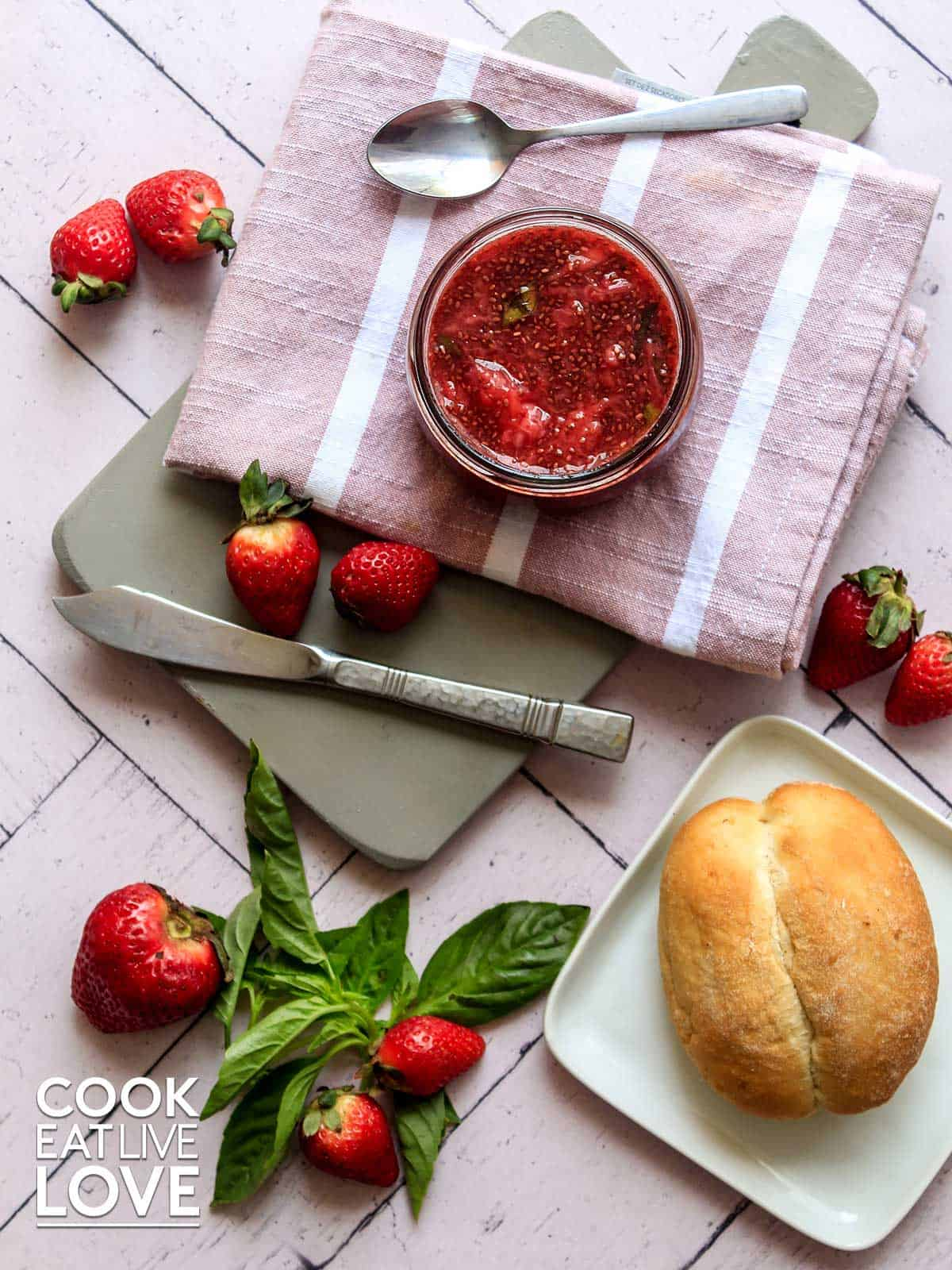Jar of strawberry jam on a cutting board with fresh bread an whole strawberries
