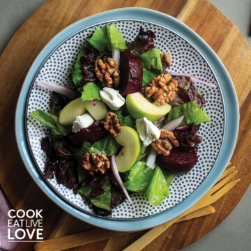 Plate of roasted beetroot salad on wooden cutting board.