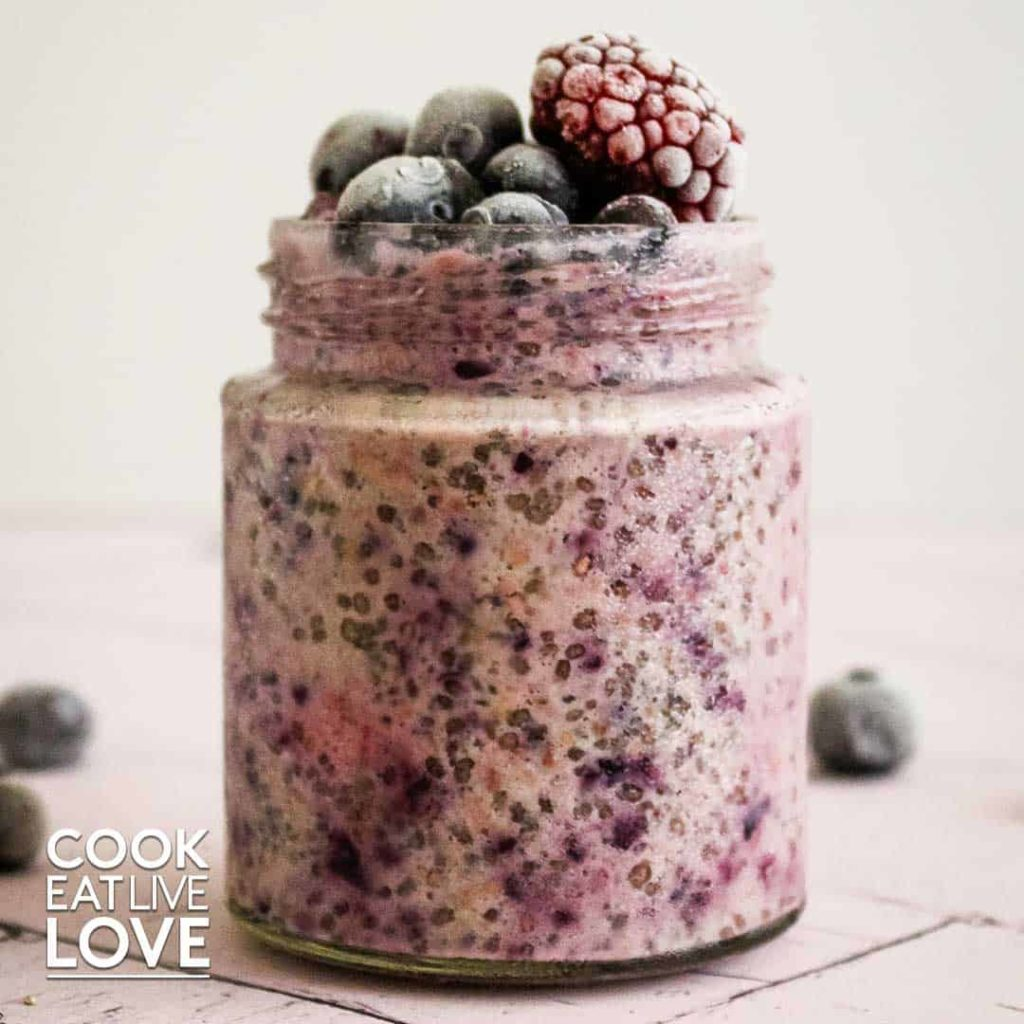 Berry overnight oats topped with frozen berries in jar