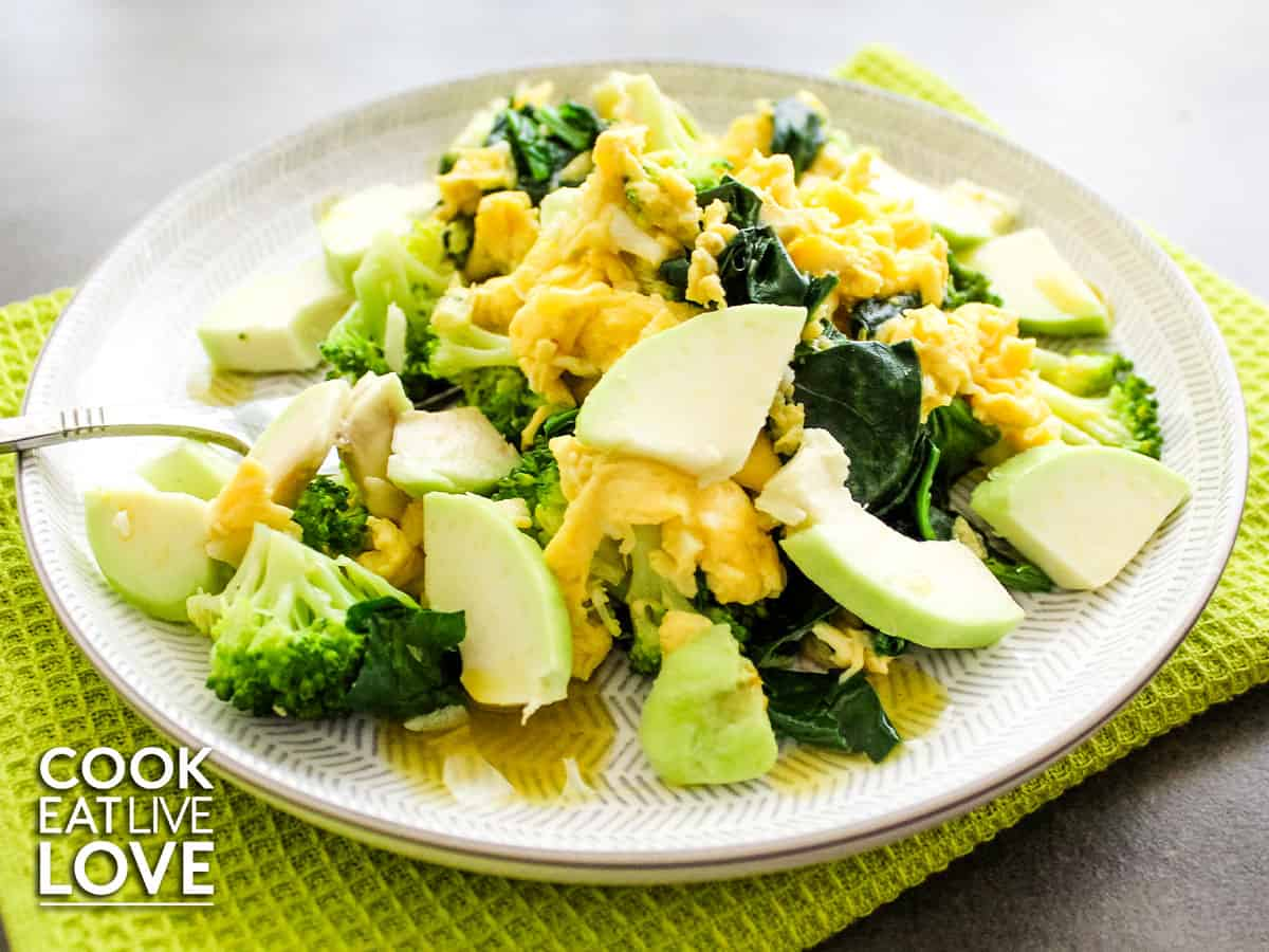 A bowl of food on a plate with eggs, avocado and broccoli